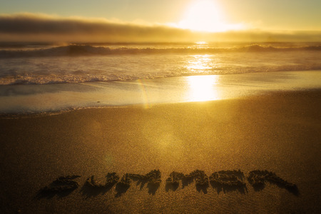 Sunset over the ocean and beach with the word Summer written in the sand. Season concept.