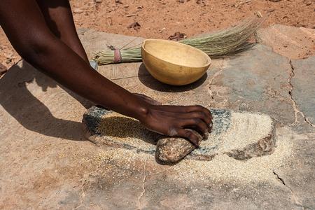 Una mujer africana moliendo cereales de mijo en harina con piedras de molienda tradicionales, Burkina Faso. Foto de archivo
