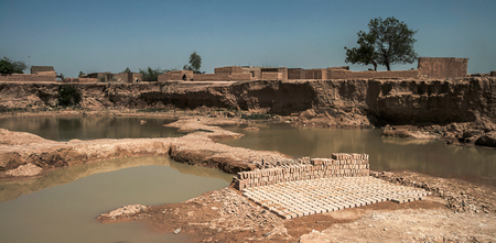 A brickyard in the slums of Ouagadougou which looks like a gigantic crater with little ponds of rainwater. Bunch of bricks of pise (compressed earth/mud) in the foreground.