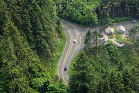 Aerial view of us route 101 at Cape Perpetua Scenic Area with resting area and traffic, winding through pine forest, Oregon, USA.
