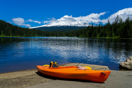 Kayak lying on the ground at Trillium Lake with the Mt. Hood in the background on a sunny day of early summer. Recreation and fishing concept advertisment.