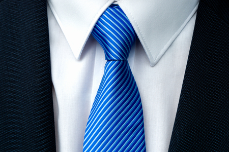 Close-up of a blue striped tie with withe shirt and dark businessman suit.