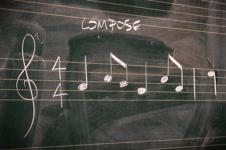 Random music notes written with chalk on a blackboard. Music composing and theory concepts.