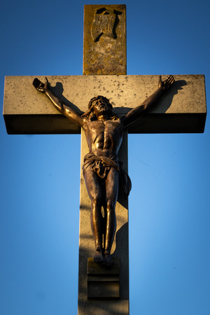 Beautiful stone cross crucifix with Jesus Christ bronze sculpture hit by sunset light on a blue sky. Stock Photo