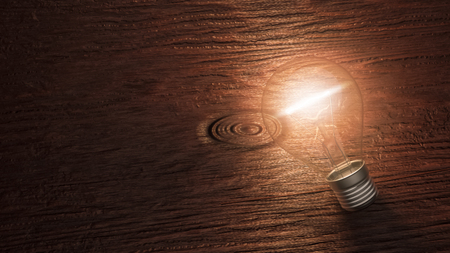 Lit up light bulb lying on a wooden background with copy space. Conceptual 3d rendering illustration.