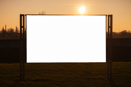 White blank advertising billboard in a park at sunset with shining sun.
