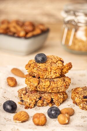 Homemade oat bran cookies with blueberries, hazelnuts, almonds, and walnuts. Healthy food. Vertical composition.