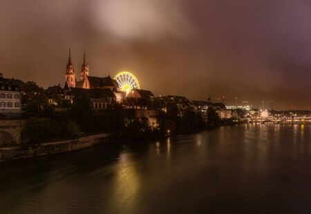 Dramatic night cityscape of the Basel old town skyline from the Rhine river, Switzerland.