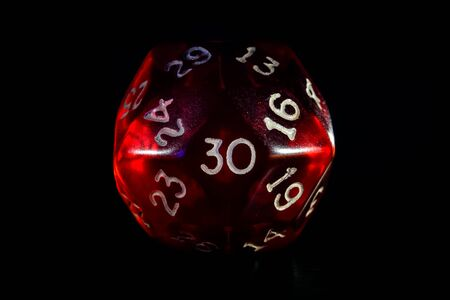 Red role playing game or rpg 30 or thirty sided dice close-up isolated on black. Stock Photo
