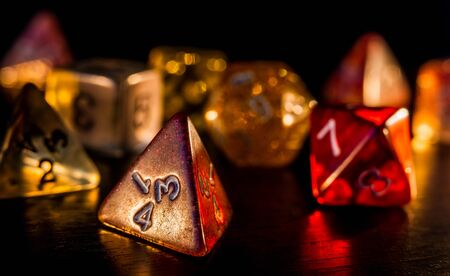 Colorful and shiny role playing dices close-up on a dark background. RPG or board game concept.