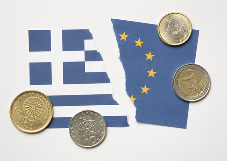 greek coins: KETTERING, UK - JULY 09, 2015: Greek Euro exit concept of torn Greek and European flags with Euros and Drachma coins photographed from above.