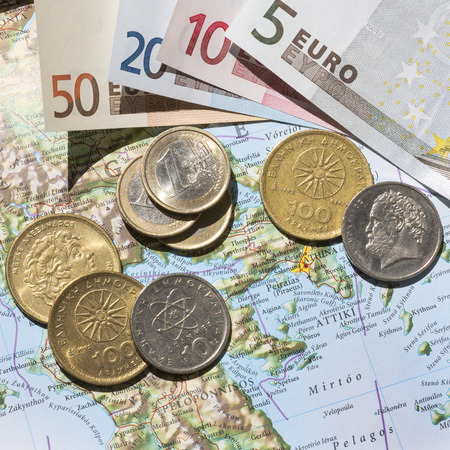 greek coins: KETTERING, UK - JUNE 24, 2015: Greek Euro exit concept of a Greek map with Euros and Drachma coins photographed with bright highlights and shadows for dramatic effect, from above.
