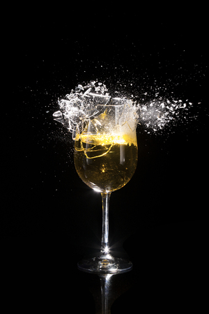 A wine glass shattering against a black background