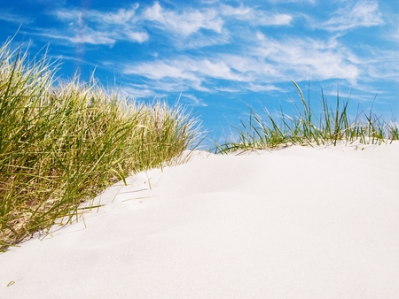Sand dune on the beach, blue sky with clouds