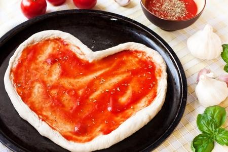 Heart-shaped pizza dough with tomato sauce
