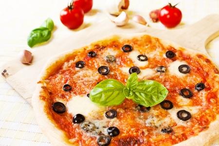 Italienische Pizza Margherita mit Oliven, Mozzarella, Knoblauch und Basilikum