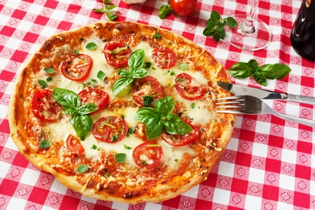 Italian Pizza Margherita with basil and fresh tomatoes photo