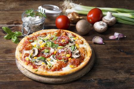 Hausgemachte Pizza mit Gemüse und frischen Kräutern