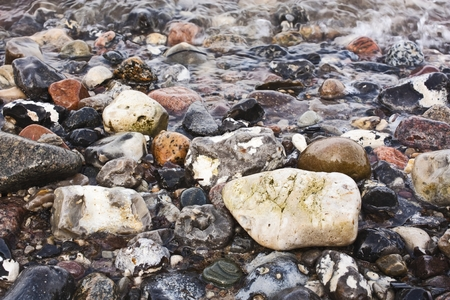 Different colored pebble stones in water Stock Photo