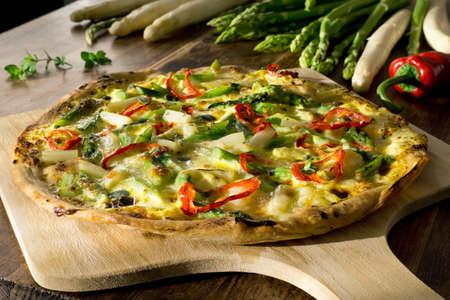 Homemade pizza with asparagus, red pepper, hollandaise sauce, mozzarella and fresh oregano