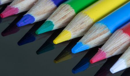 close up of coloured pencil cayons on a reflective surface