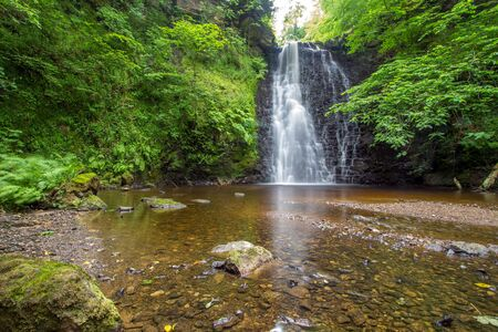 Large cascading waterfall tumbling into a peaceful pool. Falling foss waterfall, Yorkshire Dales