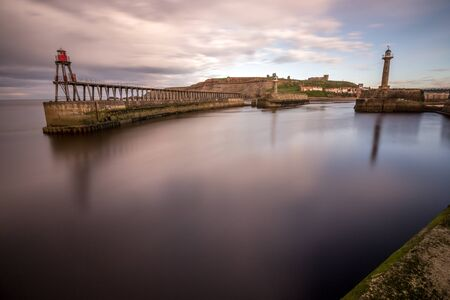 Dusk at Whitby harbour from the end of the pier. Long exposure and calm water. Stok Fotoğraf