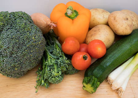Fresh, healthy organic vegetables from a farmers market on a wooden chopping board