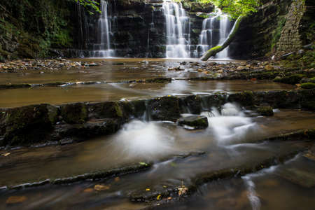 Hidden cascading waterfall in a deep gorge with trickling white water. Forest of Bowland, Ribble Valley, Lancashire