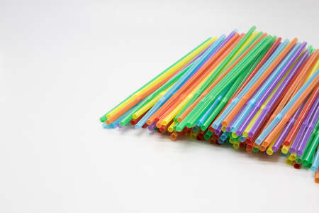 Multicoloured plastic straws on a white background with copy space