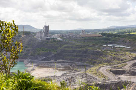 Large limestone quarry in Clitheroe, Ribble valley. Excavators and trucks working to excavate rocks Imagens