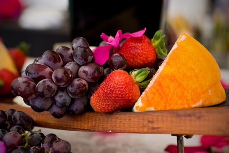 An appetizer selection of cheese, crackers, grapes and strawberries