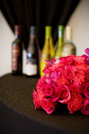 A series of five wine bottles set behind a flower arrangement Stock Photo