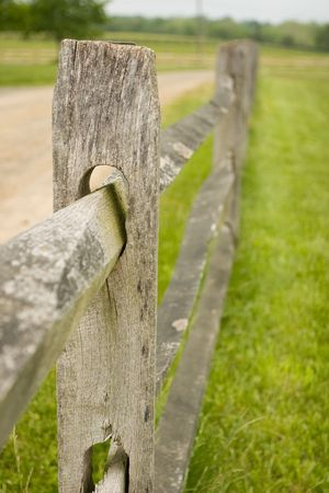Old rustic wooden picket fence on a farm next to a dirt road  Banco de Imagens