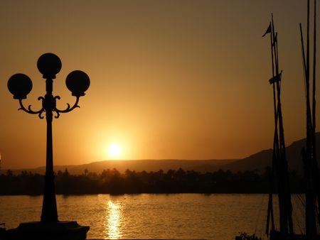 Sunset over the river nile luxor egypt with sillhouetted lamp photo
