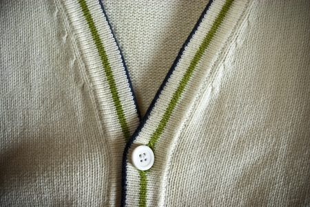 Bright beige cardigan sweater with blue and green stripes and buttons background or texture photo