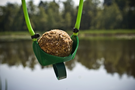 Ball of groundbait in slingshot ready to shoot and feed fish  Fishing concept photo
