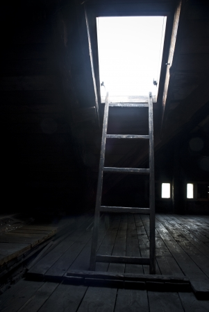 Ladder and roof window in wooden attic photo