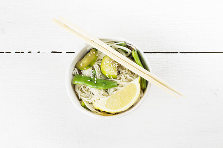 haricot: Asian noodles with siliculose haricot, zucchini and lemon on white wooden background. Top view