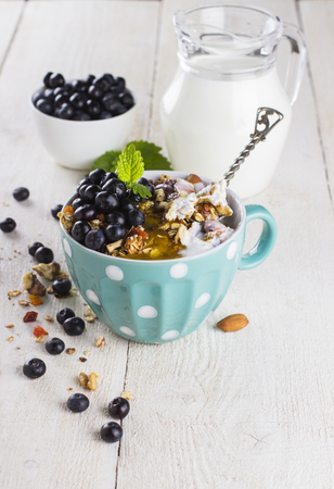 breakfast bowl: granola with blueberry, mint, honey and milk in blue bowl with milk jug on a white table and metal spoon