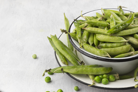 uncooked: Green peas in metal bowls on a white background