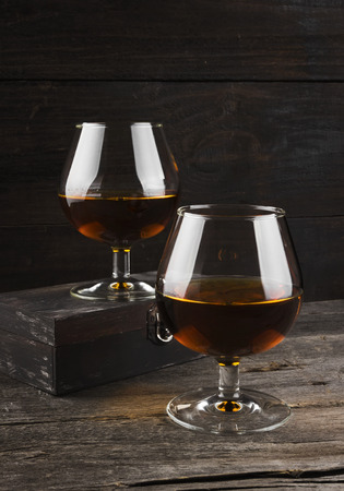 cognac: Cognac in two glasses on a dark wooden background