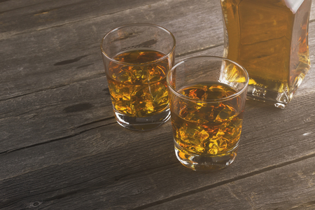 Whisky in two glasses on a dark wooden background. Toning. Stock Photo