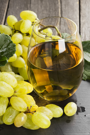 White wine and grapes on a dark background.