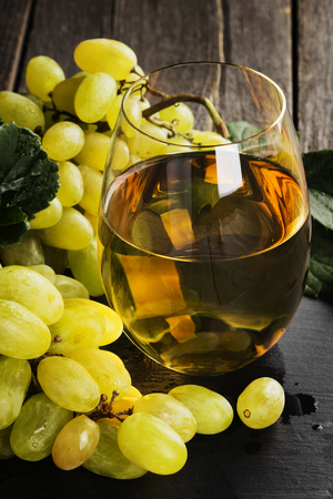White wine and grapes on a dark background. Toning.
