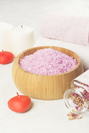 aroma bowl: Bath salt with aroma of a rose in a wooden bowl, petals and a fresh pink rose, towels and candles on a white background. Toning.