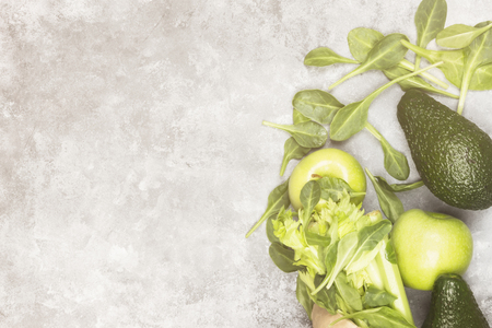 Various green vegetables and fruit - celery, apples, avocado, spinach in a paper package on a light background. Top view, copy space. Food background. Toning.