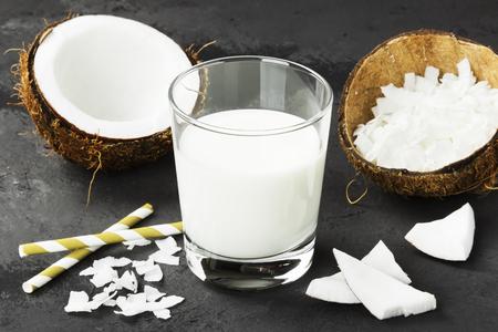 Vegan coconut milk in glass on a dark background. Non-dairy milk Stock Photo