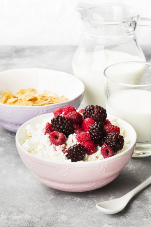 Cottage cheese in bowl with frozen raspberry and blackberry and milk in glass on a light background