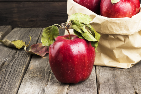 Apples in paper package on a dark wooden background Stock Photo